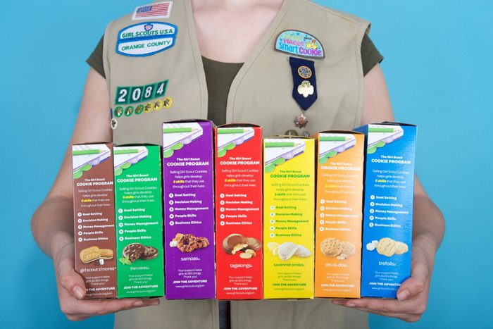 Cadette Girl Scout holding boxes of Girl Scout cookies.