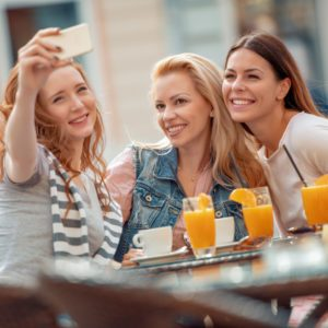 Friends having a great time in cafe.Friends smiling and sitting in a coffee shop, drinking coffee and enjoying together.; Shutterstock ID 1131394877; Job (TFH, TOH, RD, BNB, CWM, CM): TOH Girls Getaway