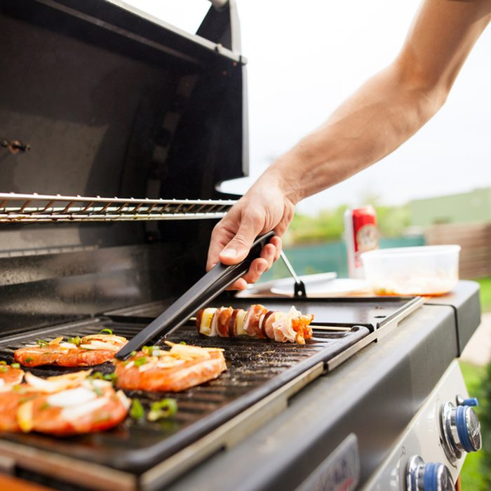 Hand of young man grilling some meat and vegetable-meat skewers on huge gas grill