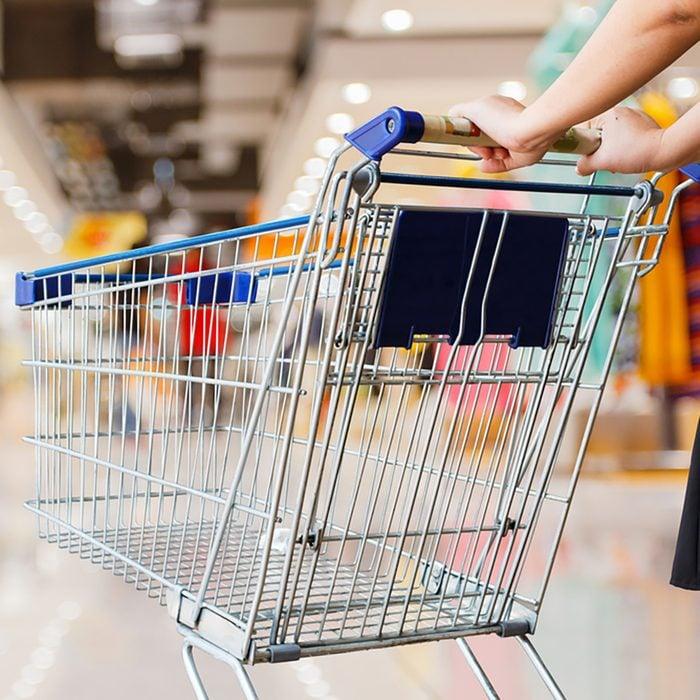 woman pushing shopping cart in shopping mall;