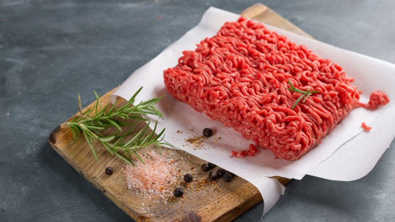 Minced meat on butcher paper with basil and pepper