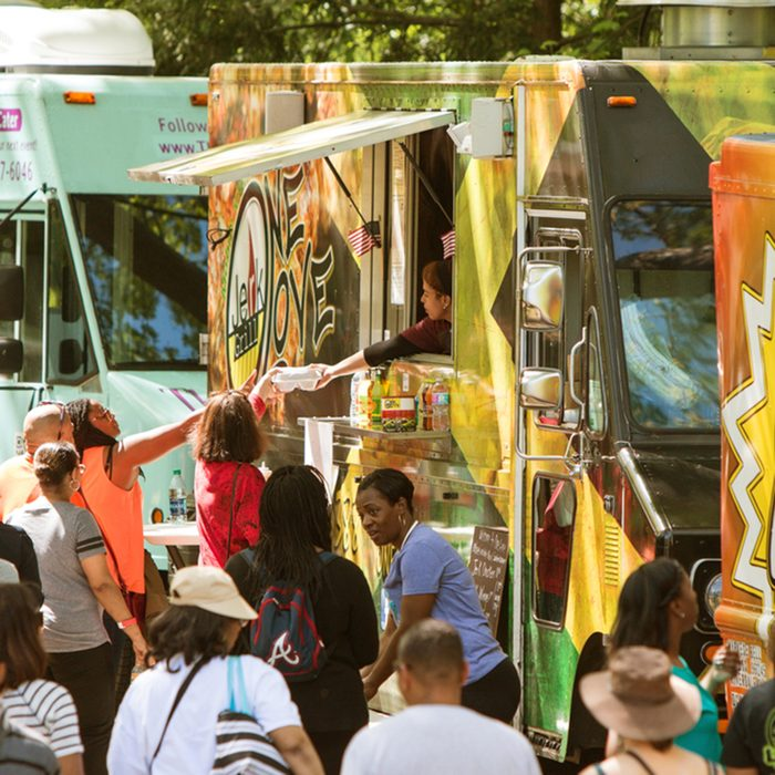 A crowd of people buy meals from food trucks lined up in Grant Park at the Food-o-rama festival