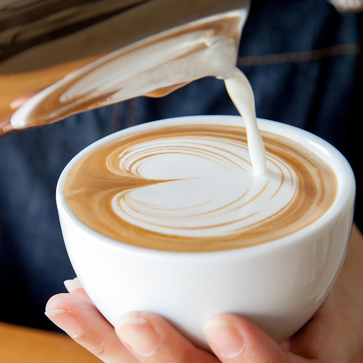 Person pouring milk into their coffee