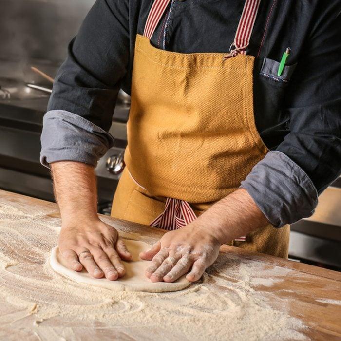 Male chef preparing dough for pizza in restaurant kitchen