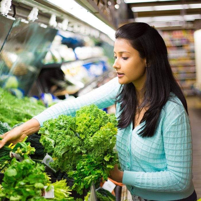 pretty young woman in sweater picking up, choosing green leafy vegetables in grocery store