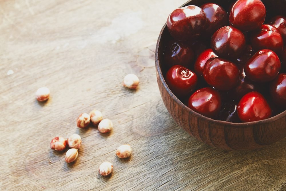 Photo of cherry berries in the wooden bowl on the wooden table and fruit pits near it