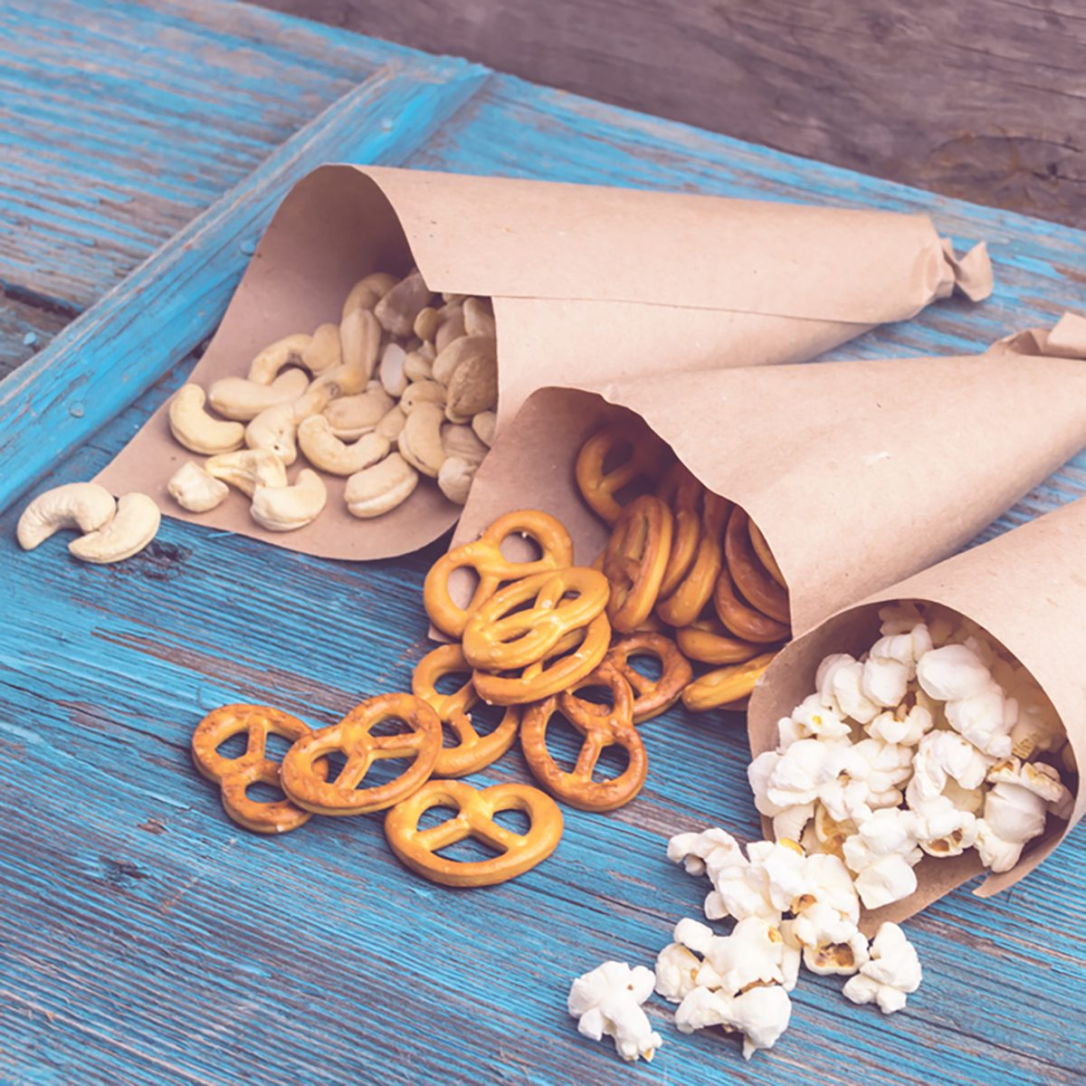 A variety of nutritious snacks ,nuts, crackers, popcorn , paper bags, lying on a wooden table;