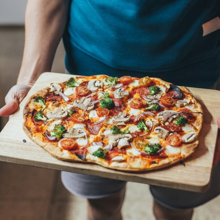cook holds wooden tray or board with homemade organic flatbread pizza, covered with vegetables, veggies and cheese