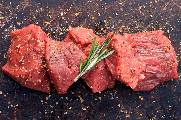 Raw beef cubes with rosemary and beefsteak spices on brown rustic background