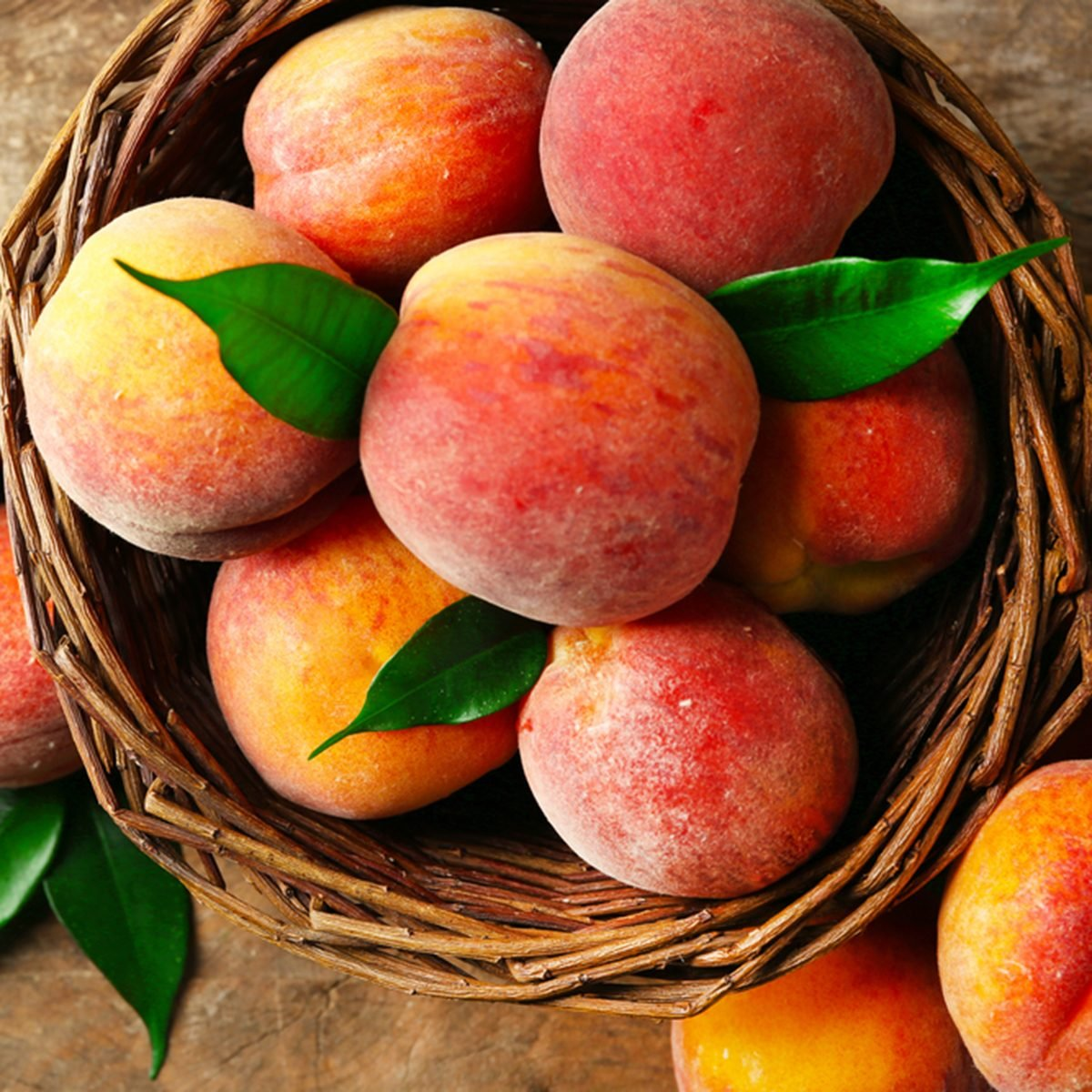 Ripe peaches in basket on wooden background
