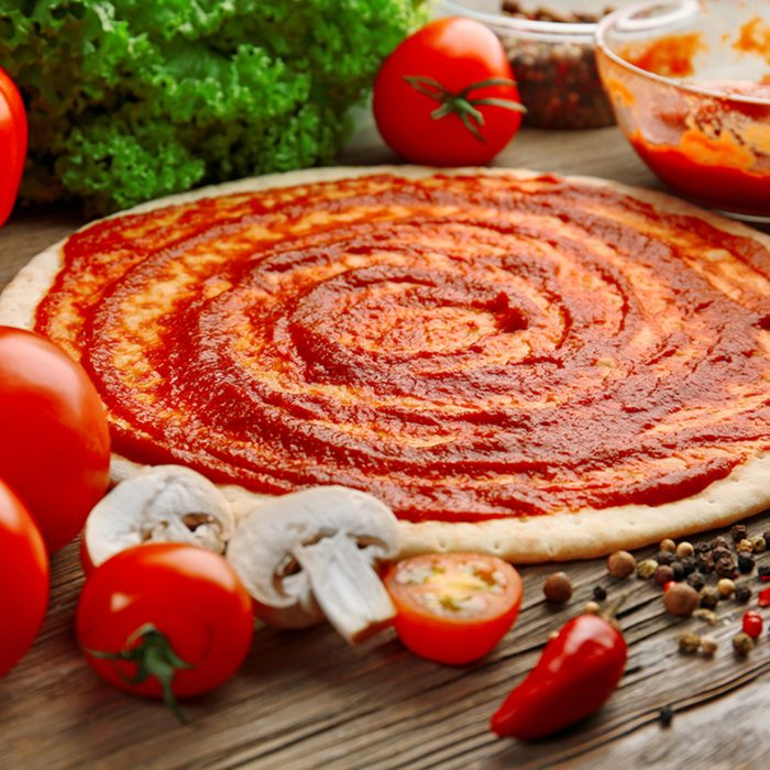 Dough basis with ketchup and ingredients for pizza