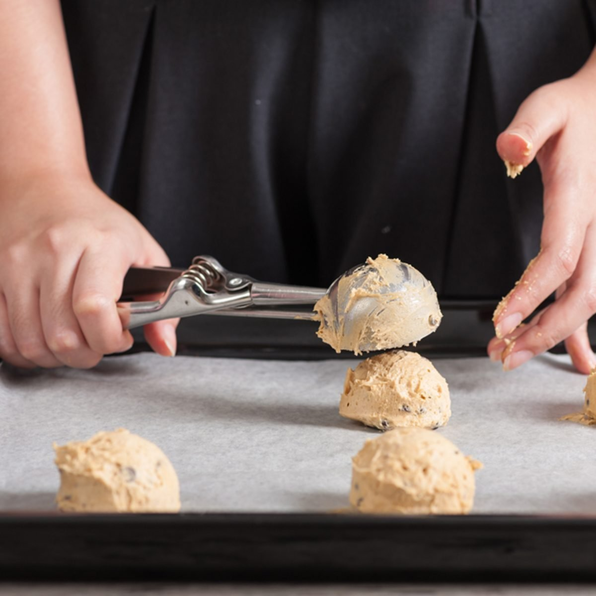 Putting mixed cookie ingredients into tray