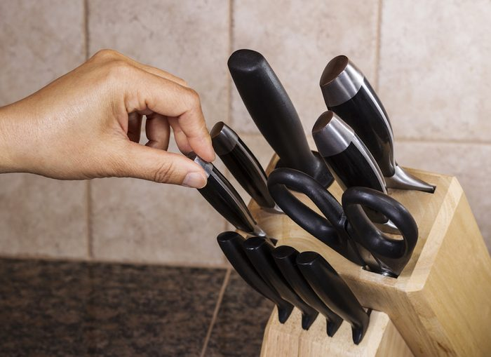 Hand selecting knife out of full set on kitchen counter top; Shutterstock ID 111078305