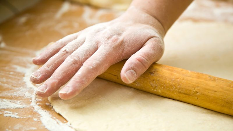 hand with rolling pin and flour;