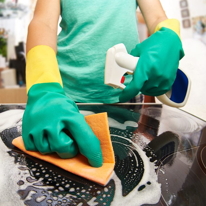 Young woman cleaning stove in her kitchen; Shutterstock ID 247066327; Job (TFH, TOH, RD, BNB, CWM, CM): Taste of Home