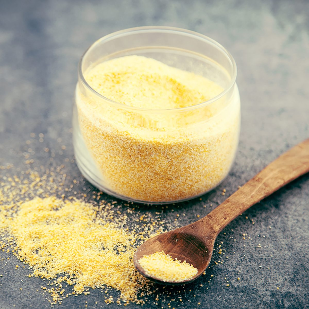 Yellow corn flour in a glass jar on a rustic table.