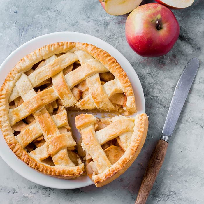 Popular American apple pie piece and cup of tea on gray table background.