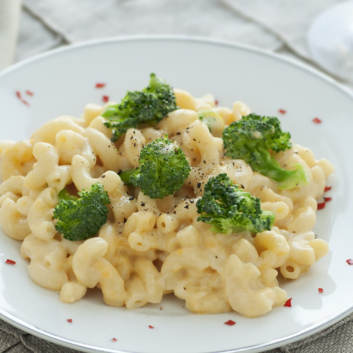 White plate of fresh homemade macaroni and cheese with broccoli and red pepper