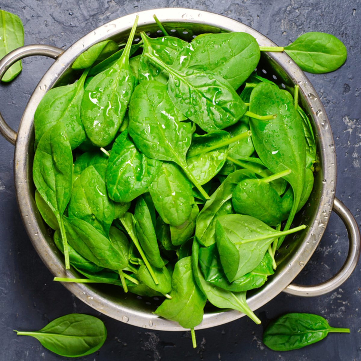 Washed fresh mini spinach in a colander on the old concrete table