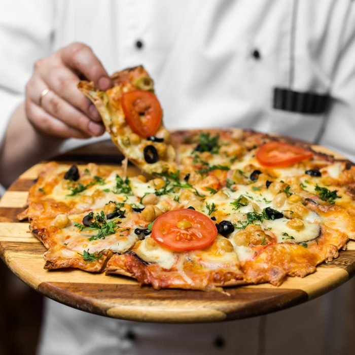 White Wood Fired Neapolitan Pizza Maker Close Up Holding Silver Tray with Fresh Pie