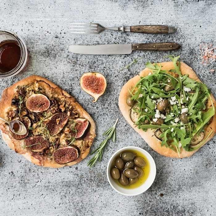 Rustic homemade pizzas with eggpant, cheese, olives, arugula, prosciutto and figs over grunge backdrop.