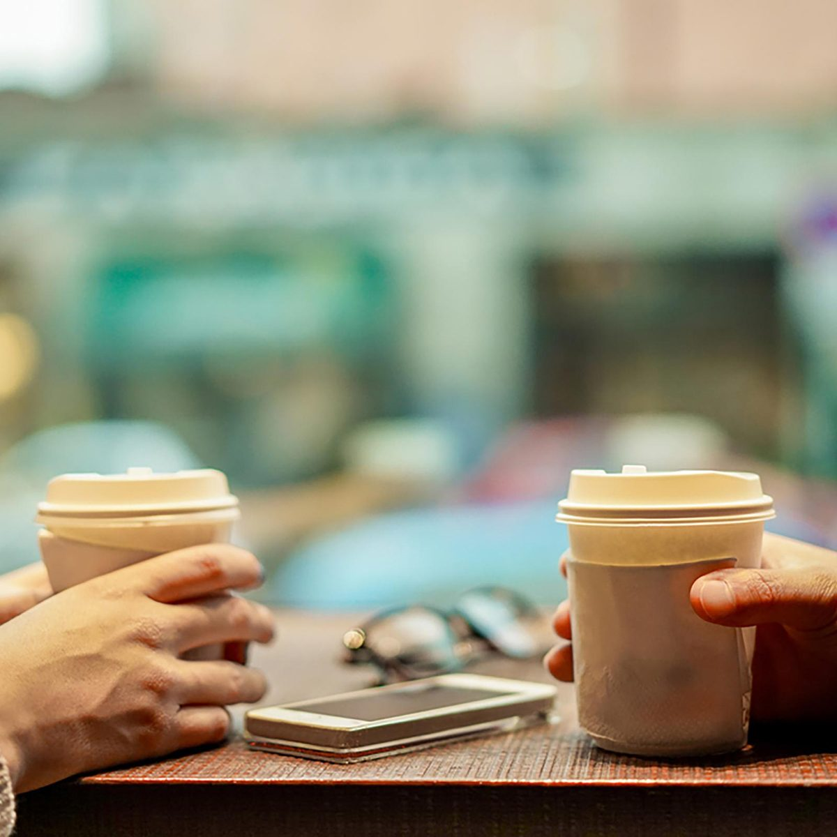 Two people sitting at table drinking coffee