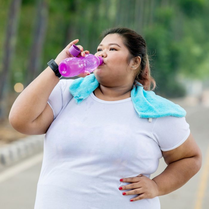 Picture of obese woman drinking water after jogging on the road