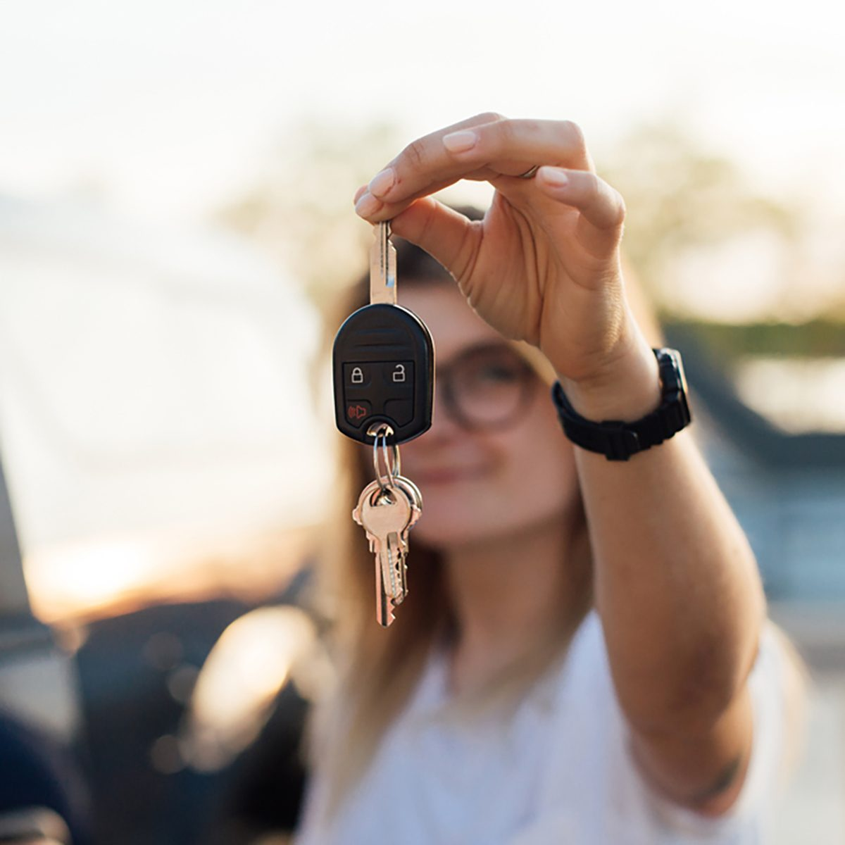 Independent young millennial hipster proudly shows keys from her car
