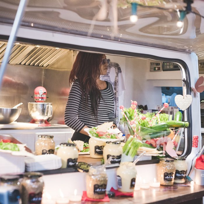 Woman inside her food truck waiting for customer