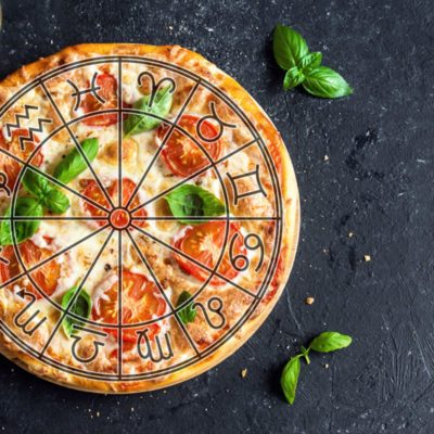 Pizza Margherita on black stone background with zodiac symbols overlay