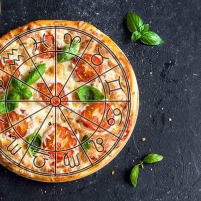 Pizza Margherita on black stone background with zodiac symbols overlay