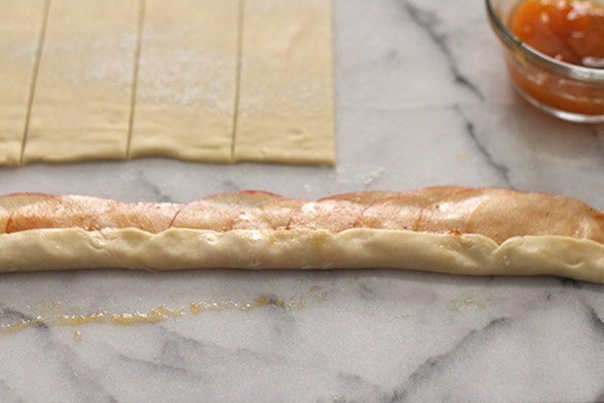 Folding dough over apple slices
