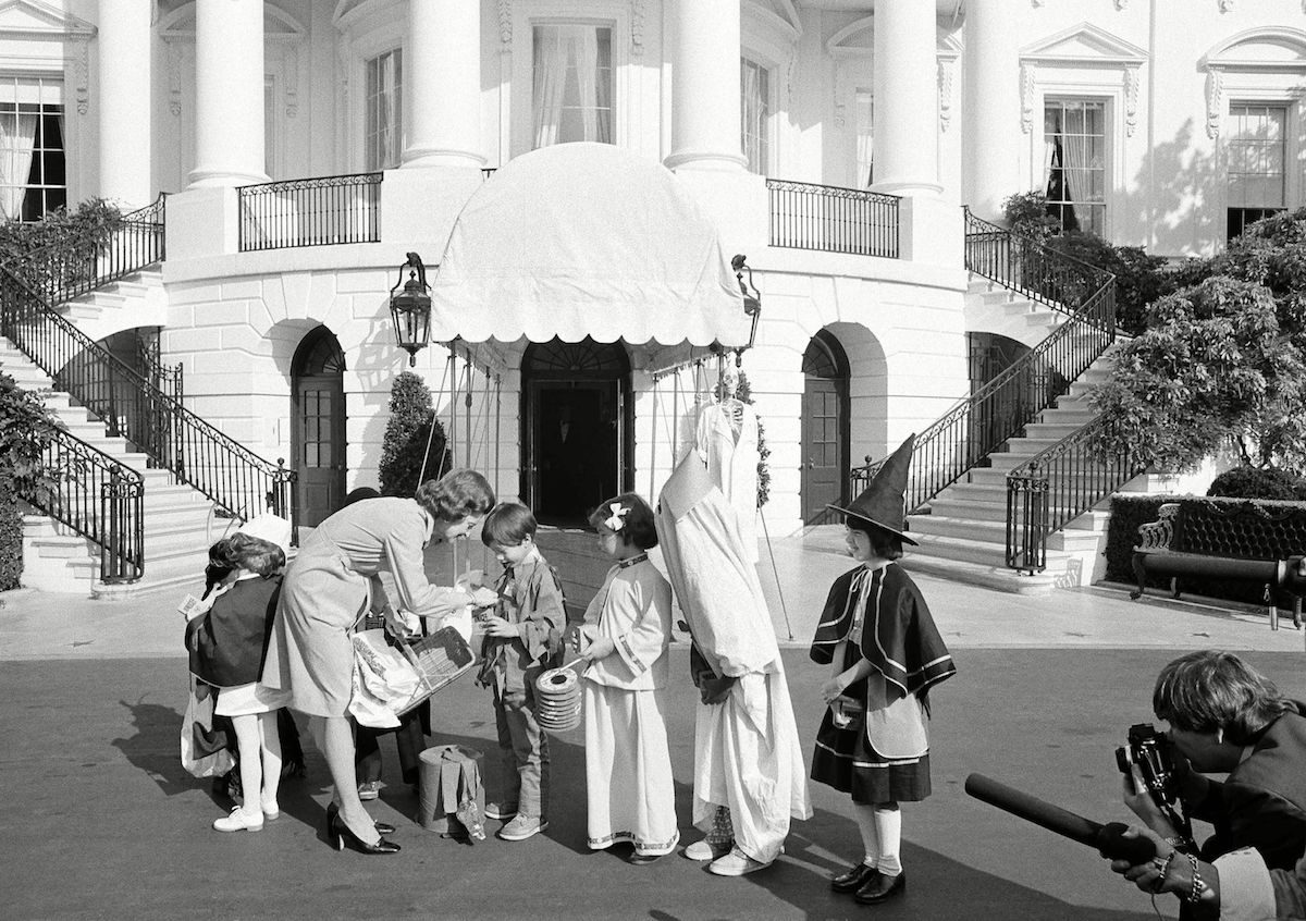 First lady Betty Ford greets costumed school children from the Washington area during a Halloween benefit for the United Nations International Children's Emergency Fund on the White House South Lawn. Mrs. Ford gave each of the children a bag of trick-or-treat candy, an apple, and reached into her pocket to put a quarter coin into the UNICEF collection boxes they carried Betty Ford Halloween, Washington, USA