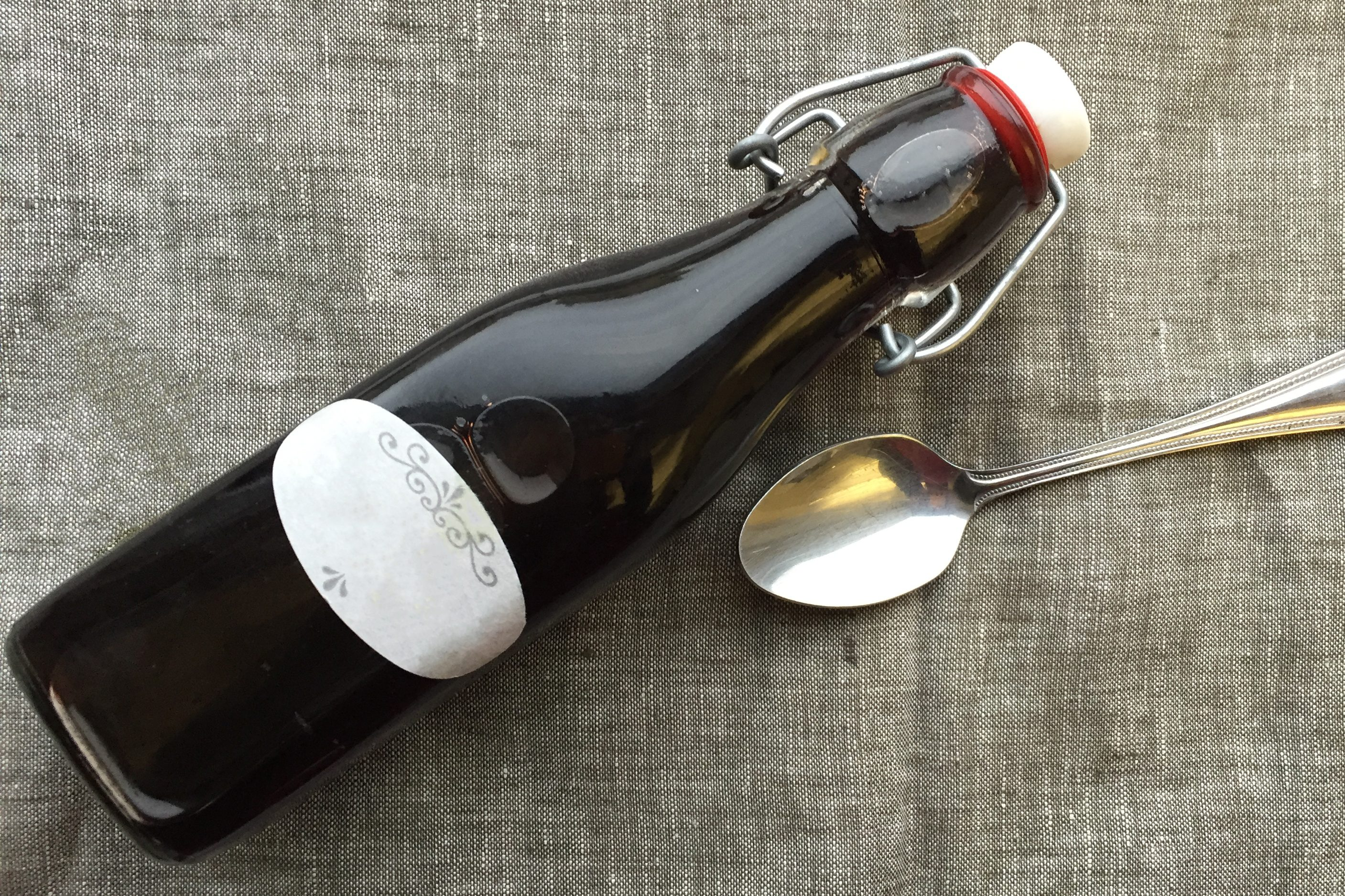 bottle of elderberry syrup with a spoon