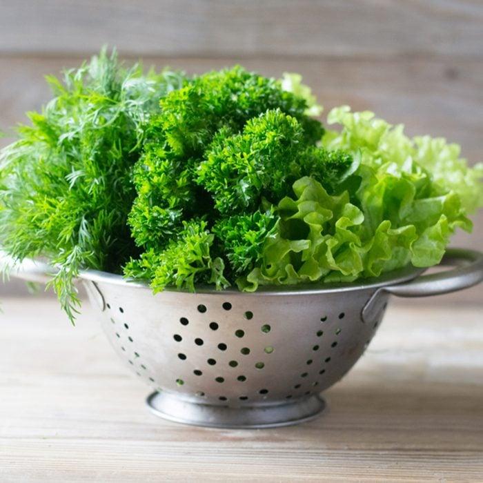 Green leafy fresh vegetables in colander
