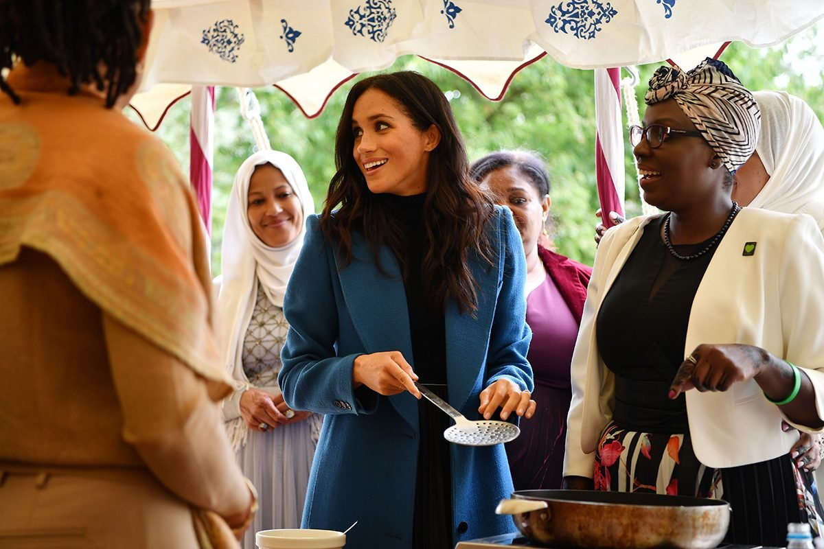 Meghan Duchess of Sussex helps to prepare food at the launch of a cookbook with recipes from a group of women affected by the Grenfell Tower fire at Kensington Palace