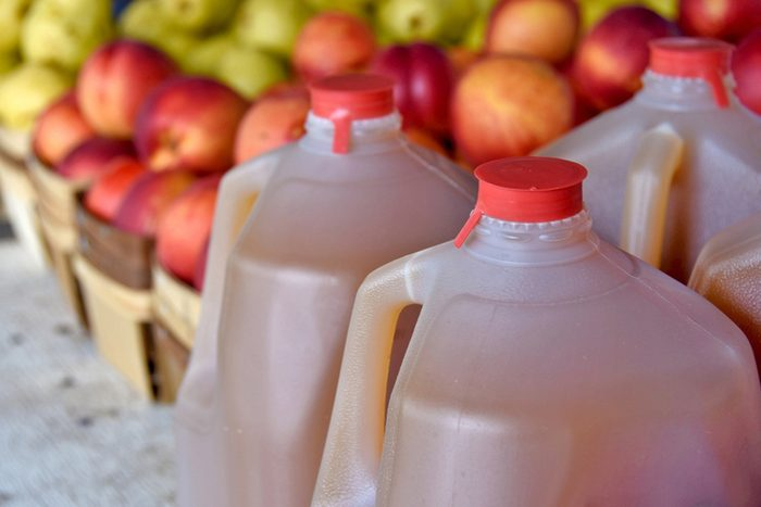 apple cider in plastic jugs with apples in produce boxes at the farmers market
