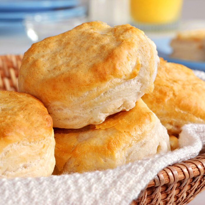 Basket of freshly baked biscuits with orange juice and tableware in background.