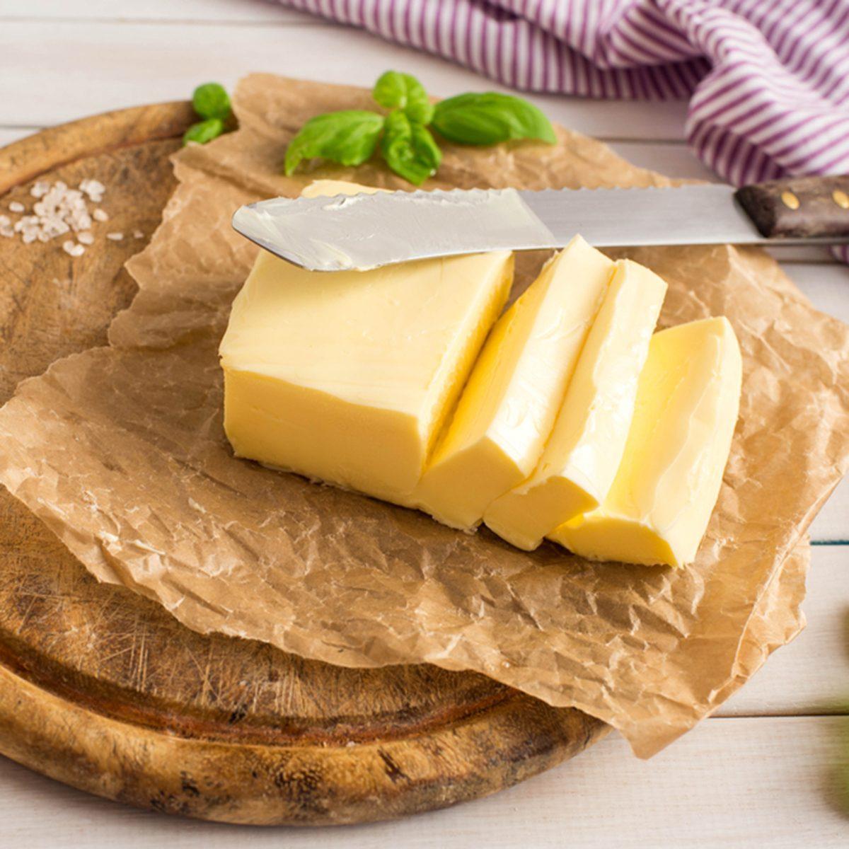 Slice of butter. Fresh sliced butter on the wooden plate.