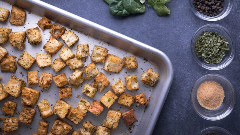 Top down view on baked bread croutons in the corner of a metal rimmed baking sheet