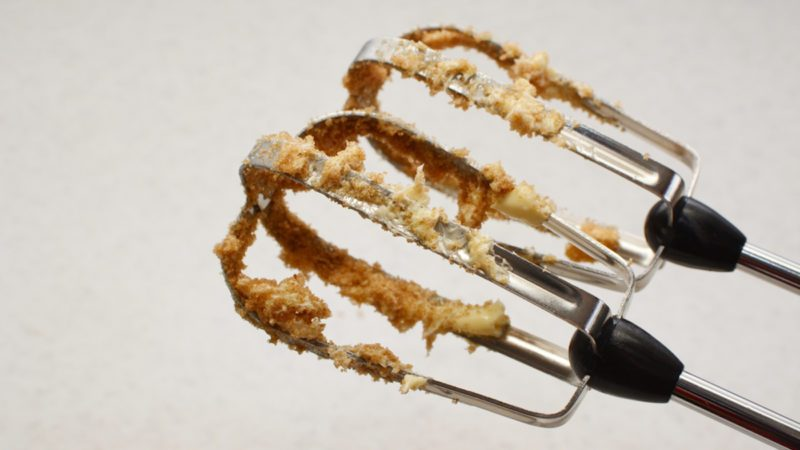 Closeup of electric whisk beaters covered in butter and muscovado sugar