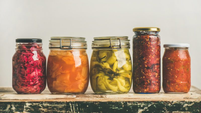 Autumn seasonal pickled or fermented colorful vegetables in jars placed in row over vintage kitchen drawer