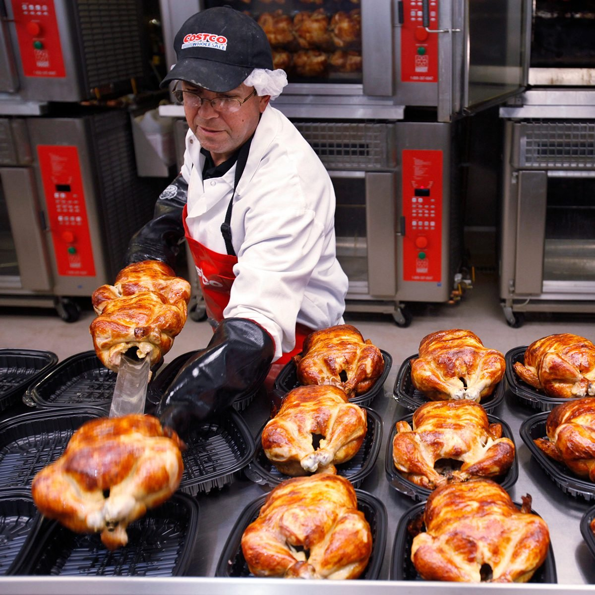 A Costco employee cooks chicken at Costco in Mountain View, Calif.