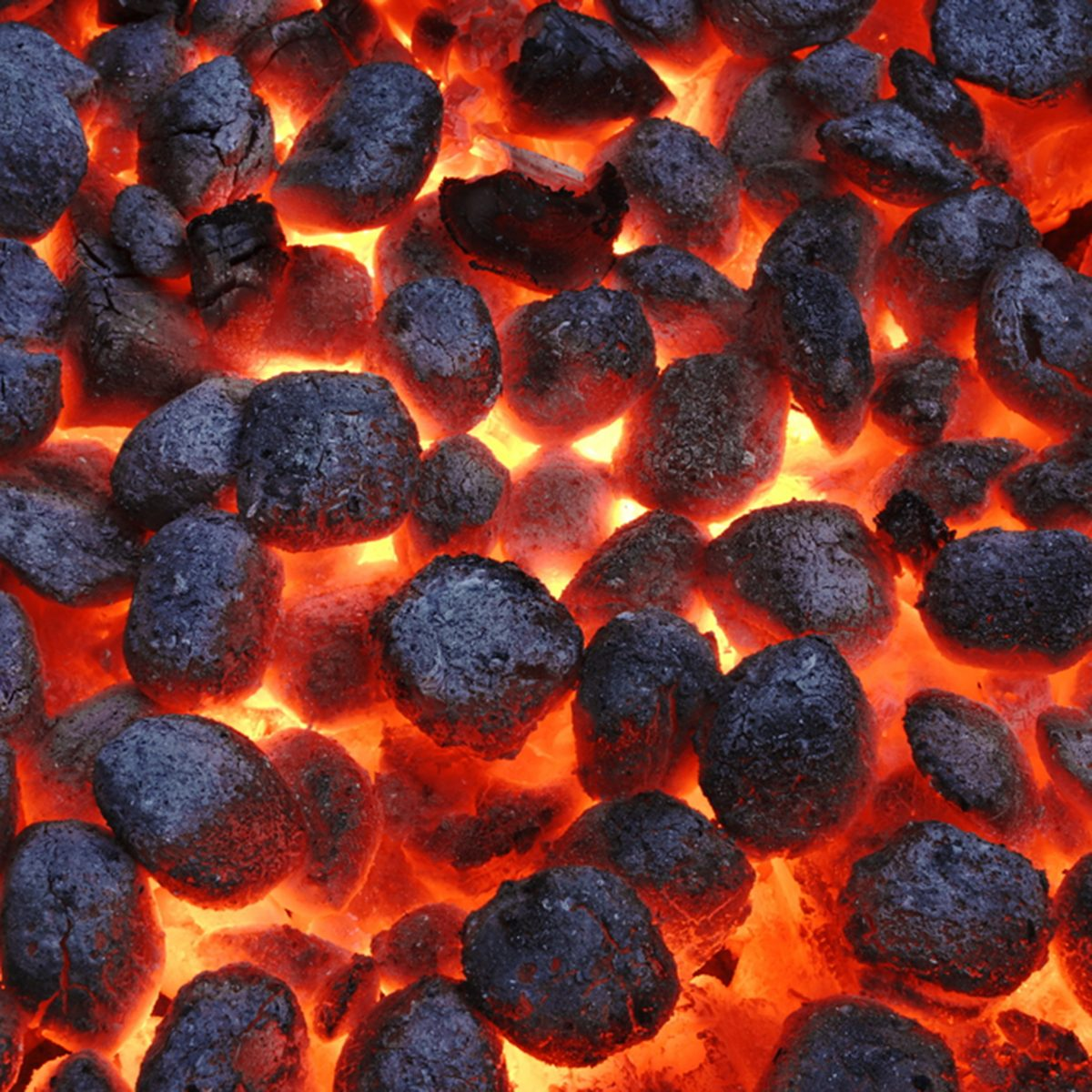 BBQ Grill Pit With Glowing And Flaming Hot Charcoal Briquettes