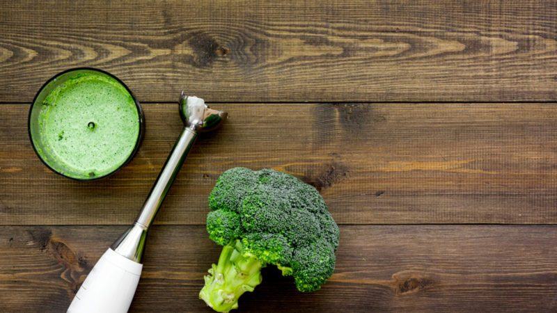 Broccoli and blender on dark wooden table