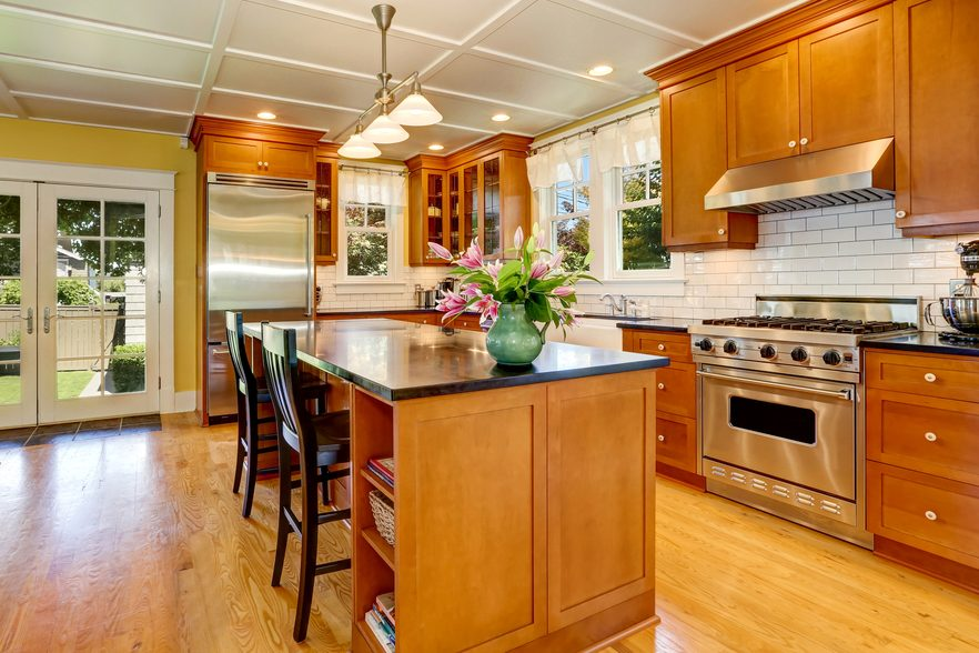 Design of brown wooden kitchen with steel appliances. Bar style kitchen island with bouquet of fresh flowers and pendant lights. Northwest, USA