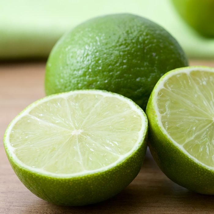 Close-up of cutted green limes on a wooden background.