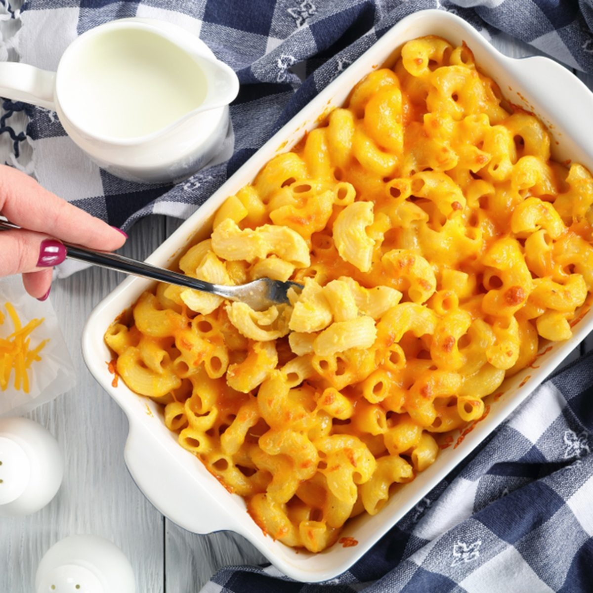 woman's hand is holding a fork with small portion of Mac and cheese or elbow pasta baked with cream and sharp cheddar cheese sauce in dish,
