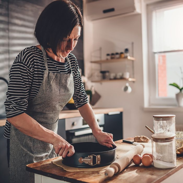 Woman preparing apple pie crust dough in the kitchen by the old wooden table