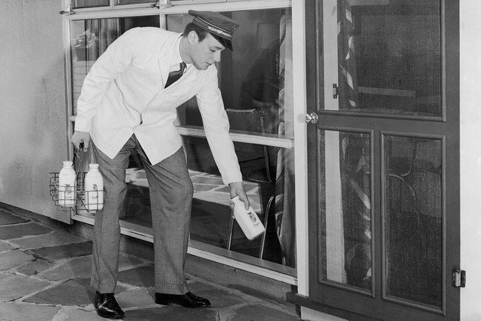 Milkman delivering milk door to door